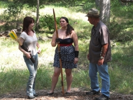 John Daws offers archery training to Nina (Celeste Coburn). Rose (Tiffany Patch) assists .